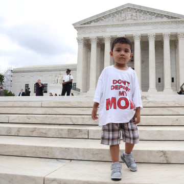 A boy wears a t-shirt reading 'Don't deport my mom'