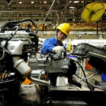 An employee works on an assembly line producing automobiles at a factory in Qingdao