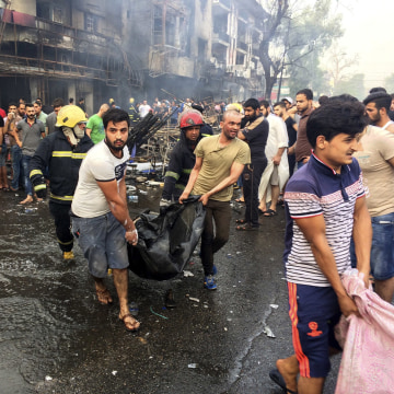 Image: Iraqi firefighters and civilians carry bodies of victims killed in a car bomb