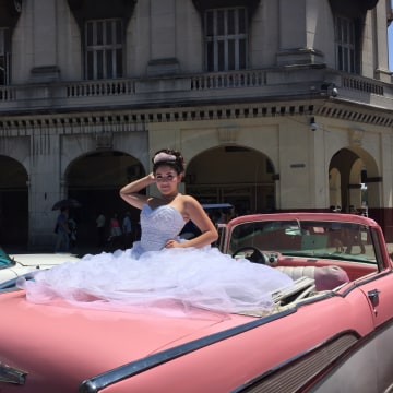 "Cuban girl poses in a 1957 Chevrolet Bel Air convertible during her ""quinceañera"" celebration."