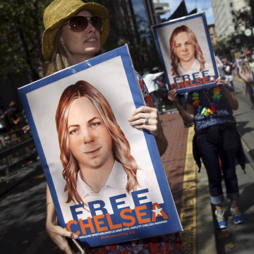Image: People hold signs calling for the release of imprisoned wikileaks whistleblower Chelsea Manning while marching in a gay pride parade in San Francisco, California