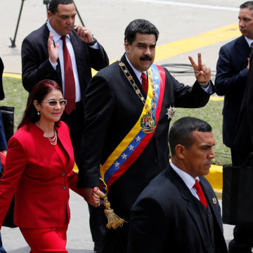Venezuela's President Nicolas Maduro flashes the victory sign to the media next to her wife Cilia Flores in Caracas, Venezuela July 5, 2016.