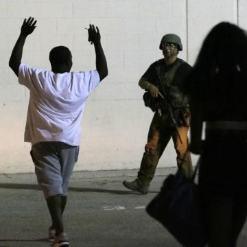 Image: A man raises his hands as he walks near a law enforcement officer