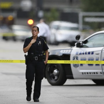 Image: A Dallas Police Officers guards the scene of a shooting