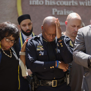 Image: Dallas Police Chief David Brown prays during a a vigil at Thanks-Giving square in Dallas