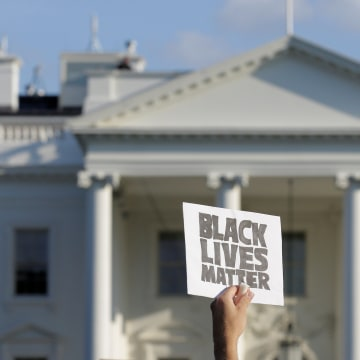 Image: A demonstrator with Black Lives Matter holds up a sign during a protest in front of the White House in Washington.