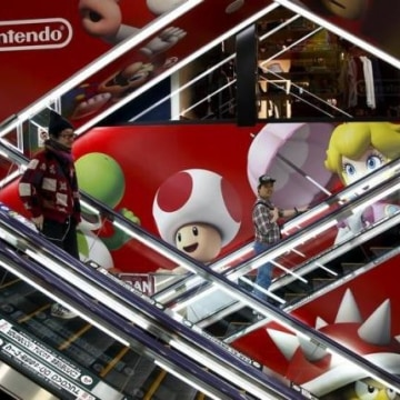 People ride escalators past an advertisement of the Nintendo Co videogame maker at an electronic retailer in Tokyo