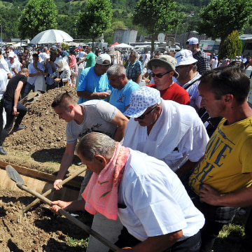 Image: Bosnian Muslims, survivors of Srebrenica 1995 massacre, bury body caskets with remains of their relatives