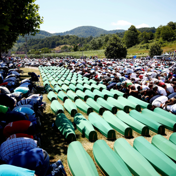 Image: Muslim men pray in front of coffins during mass funeral in Potocari near Srebrenica