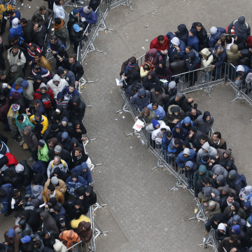 Image: Migrants line up outside Office of Health and Social Affairs as they wait to register in Berlin