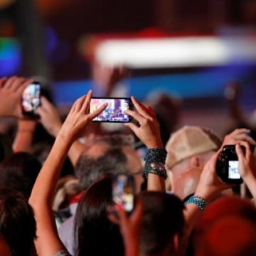 A fan uses a cell phone to record a performance during the 2014 CMT Music Awards in Nashville