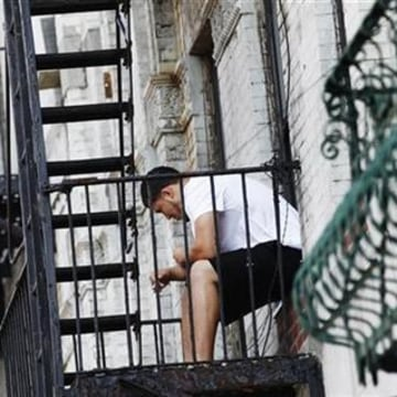 A man sits on a fire escape outside an apartment in New York