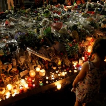 A child stands near flowers and candles placed to pay tribute to victims of the truck attack along the Promenade des Anglais on Bastille Day that killed scores and injured as many in Nice