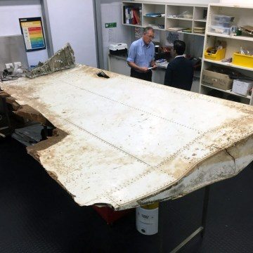 Image: Investigators examine the Pemba Island debris in this handout picture released by the ATSB.