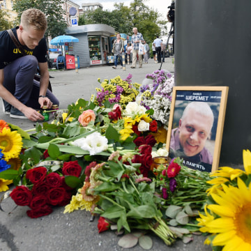 Image: A man lights a candle where journalist Pavel Sheremet was killed
