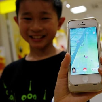 "Boy poses with a mobile phone displaying the augmented reality mobile game ""Pokemon Go"" by Nintendoa in front of a shop selling Pokemon goods in Tokyo"