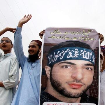 Image: Protesters hold portraits of Burhan Wani