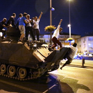 Image: People ride a tank in Istanbul, Turkey,