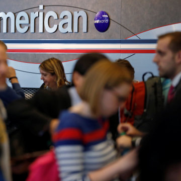 Image: Travelers line up at an American Airlines ticket counter at O'Hare Airport in Chicago
