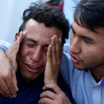 Image: An Afghan man weeps outside a hospital after a suicide attack in Kabul, Afghanistan