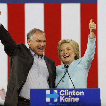 Image: Democratic U.S. vice presidential candidate Kaine waves with his presidential running-mate Clinton after she introduced him during a campaign rally in Miami