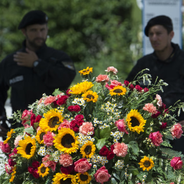 Image: Police officers stand behind a wreath near the Olympia shopping center where the shooting took place.