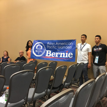 Supporters of Sen. Bernie Sanders arrive at the AAPI Caucus meeting, at the Pennsylvania Convention Center, with a banner, July 25, 2016.