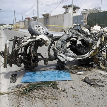 Image: Somali soldier stand near the wreckage of a car bomb outside the UN's office in Mogadishu, Somalia