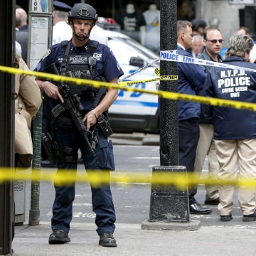 Image: Members of the NYPD police stand near the crime scene at the intersection of 37th street and 8th avenue in midtown Manhattan in New York