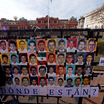 Demonstrators stand next to pictures of the 43 missing Mexican students of Ayotzinapa College in Buenos Aires, Argentina, July 29, 2016.