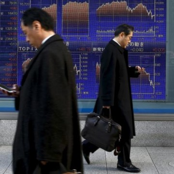 Men walk past an electronic board showing market indices outside a brokerage in Tokyo