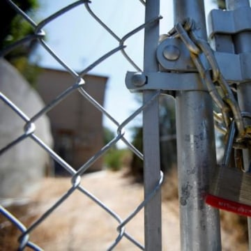 A lock secures a chain on the steel fence of a foreclosed home previously owned by U.S. Bancorp in Los Angeles