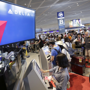 Image: Passengers check in at the Delta counter at Narita airport in Tokyo on Tuesday