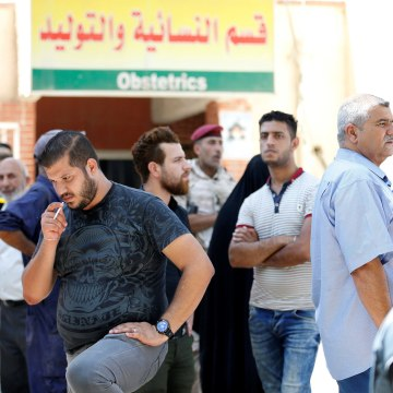 Image: People stand outside a maternity ward after a fire broke out at Yarmouk hospital in Baghdad