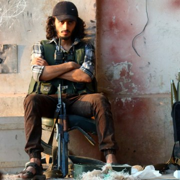 Image: A rebel fighter sits with his weapon in the artillery academy of Aleppo