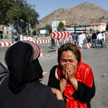 Image: An Afghan woman weeps at site of a suicide attack in Kabul, Afghanistan