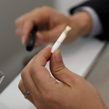 """A customer takes off a filter after trying a Philip Morris' """"iQOS"""" smokeless tobacco at an iQOS store in Tokyo"""
