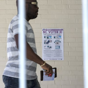 Image: Eric Gandah walking past a NC Voter ID sign as he enters a precinct to cast his ballot in Greensboro, N.C.