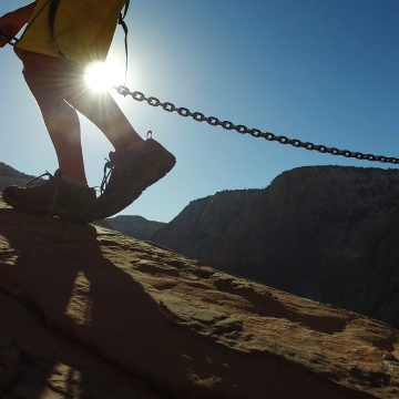 Image: A hiker climbs along the Angels Landing trail in Zion National Park