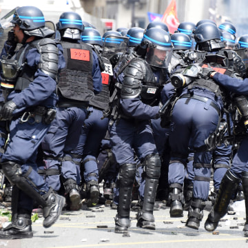Image: French police officer falls during protest against labor reforms in Paris on June 14, 2016