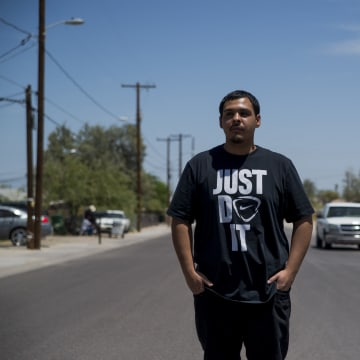David Castorena, 24, of Chandler, Arizona, stands in the street of a small, largely-Latino community where he attends church.