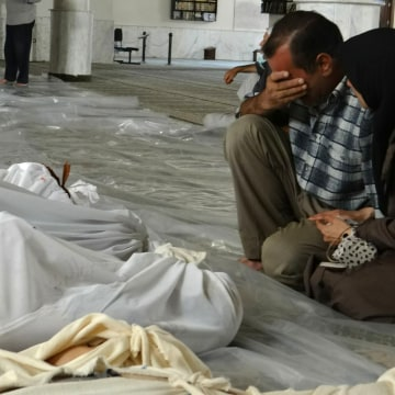 Image: A Syrian couple mourning in front of bodies wrapped in shrouds ahead of funerals following what Syrian rebels claim to be a toxic gas attack