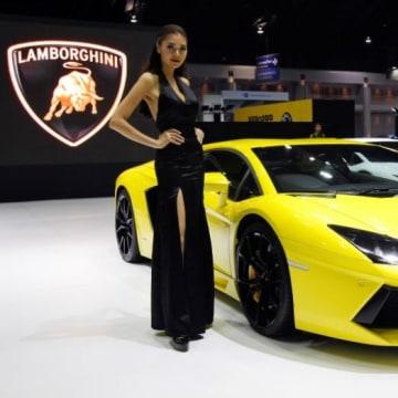A model poses beside a Lamborghini Aventador LP700-4 during a media presentation at the 37th Bangkok International Motor Show in Bangkok