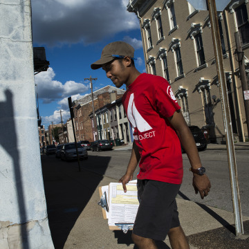 Image: Dallas Stokes, a volunteer for the AMOS Project, a nonprofit social justice organization in Cincinnati, registers people to vote