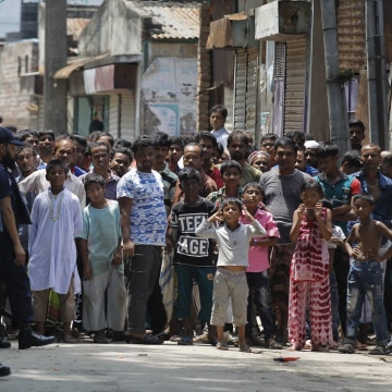 Image: Onlookers gather near the scene of the shooting in Narayanganj, Bangladesh.