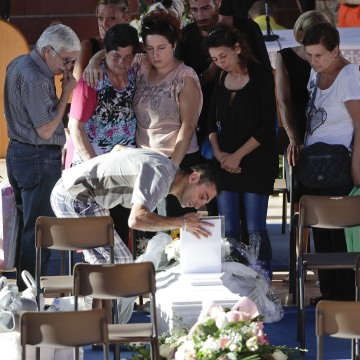 Image: Relatives mourn over a coffin of one of the earthquake victims