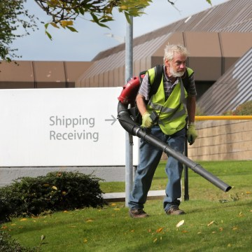 Image: A worker blows leaves away from the Apple campus in Cork, Ireland in this 2014 file photo.