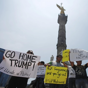Image: Demonstrators hold placards during a protest against the visit of Donald Trump in Mexico City