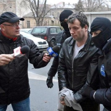 "Lehel, alleged hacker ""Guccifer"", is escorted by masked policemen in Bucharest, after being arrested in Arad"