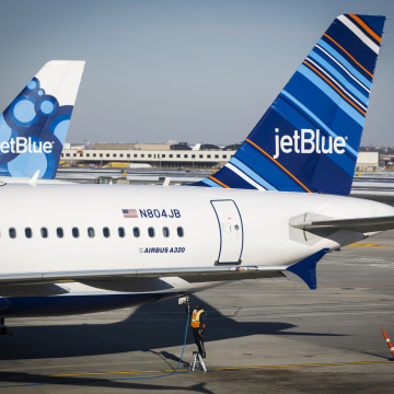 An airport worker fuels a JetBlue plane on the tarmac of the John F. Kennedy International Airport in New York